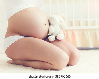 beautiful belly of pregnant young woman sitting on carpet in nursery room