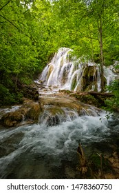 Beautiful Beusnita waterfall on Bei river in a dense deciduous forest in Romania during spring