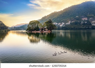 Beautiful Bhimtal lake at sunset with view of distant cityscape at Nainital Uttarakhand India.