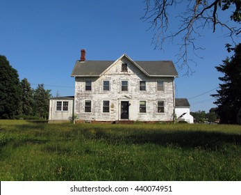 Beautiful, big, abandoned white farmhouse on a nice summer day