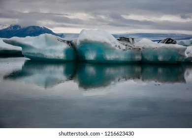 Beautiful big blue iceberg floating in Jokulsarlon glacial, Iceland in summer at dusk, reflecting in the water.