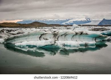 Beautiful big blue iceberg floating in Jokulsarlon glacial, Iceland in summer at dusk, reflecting in the water. Copy space available.