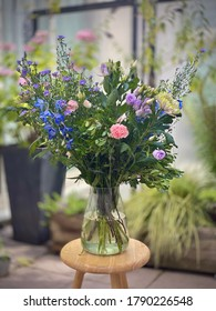 Beautiful big bouquet of flowers in a vase outside displayed on a small wooden table. Plantlife flowering standing in water. Blurred background, blue-purple and white carnations green-leafed leaves.