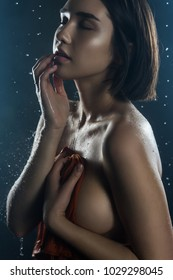 Beautiful big breasted girl covers herself with a wet shirt on a dark background. Falling rain drops and artistic scenic smoke. Advertising, commercial design. Copy space. Mixed Asian-Caucasian race.