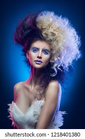 Beautiful big breasted girl with vanguard makeup and a hairstyle of black and white hair, wearing a white deep neckline dress on a blue background. Conceptual, fashion, modern and advertising design.