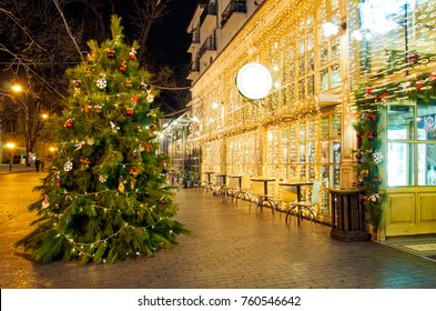 Beautiful big Christmas tree outside a cafe,decorated with golden lights, on the street with New Year decorations in the evening