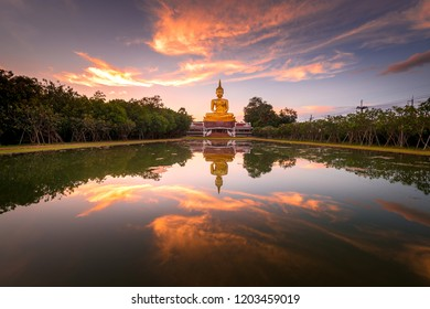 Beautiful Big Golden Buddha statue sunset sky in Thailand temple,khueang nai District, Ubon Ratchathani province, Thailand.Amazing Buddha image with sunny sky clouds.