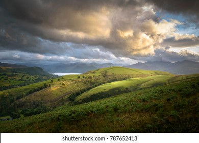 Beautiful big orange yellow cloud over green and sun lit landscape of England Lake District near Keswick