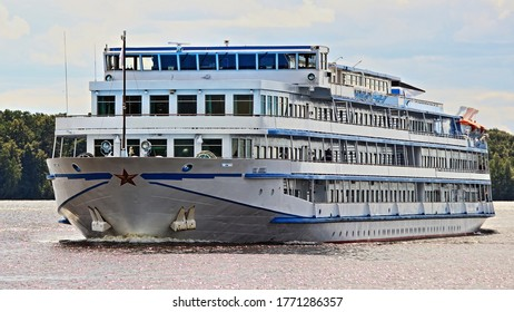 Beautiful big russian travel four deck white passenger ship cruise liner floating on water, tourist vessel front side view closeup on summer day with green trees on river Bank and blue sky background