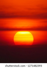 Beautiful big sunset over sea. Tranquil scene of Closeup red sun and red sky sunset over the ocean