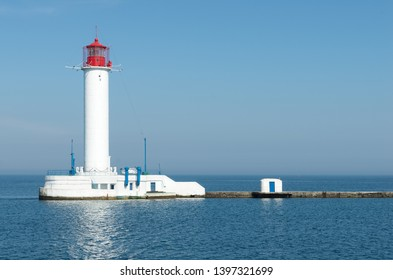Beautiful big white red lighthouse against the blue calm sea, cloudless sky and clear horizon - a symbol of the safe path for ships. Pharos on the edge of the coast. Seascape of Black sea.