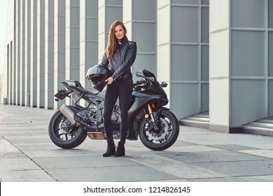 A beautiful biker girl holding helmet next superbike outside a building.