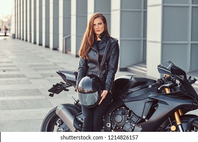 A beautiful biker girl holding helmet while leaning on her superbike outside a building.