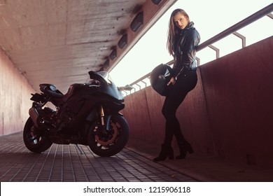 A beautiful biker girl holding helmet next superbike on a sidewalk inside the bridge.
