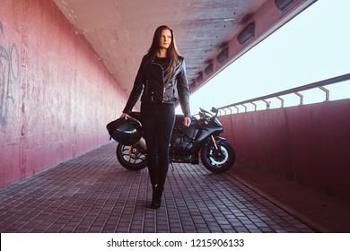 A beautiful biker girl holding helmet next superbike walks on a sidewalk inside the bridge.