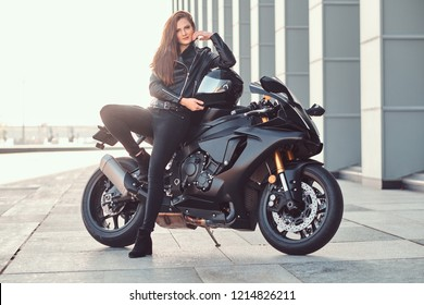 A beautiful biker girl leaning on her superbike outside a building.
