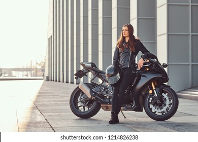 A beautiful biker girl leaning on her superbike outside a building on a sunny day.