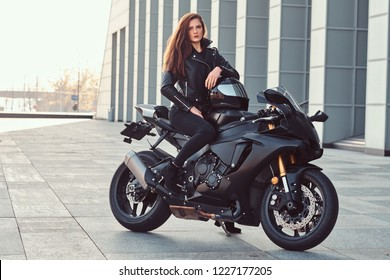 A beautiful biker girl sitting on her superbike outside a building.
