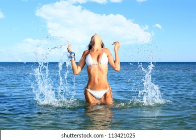 Beautiful bikini model splashing water