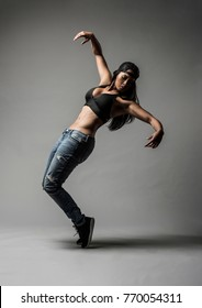 Beautiful Biracial Asian Black Dancer wearing blue jeans and baseball cap does a creative urban dance move against a grey backdrop in studio with dramatic lighting