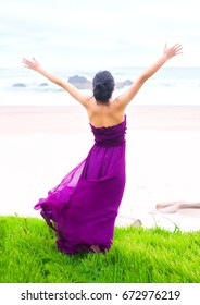 Beautiful biracial Asian Caucasian teen girl wearing purple magenta dress standing on grassy knoll overlooking ocean, arms raised