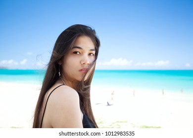 Beautiful biracial Asian Caucasian woman looking over shoulder while standing on a beach in Hawaii