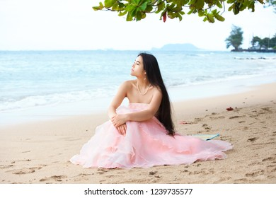 Beautiful biracial Asian Caucasian young womanwith long hair in pink gown sitting on Hawaiian beach looking out over ocean waters