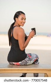 Beautiful Biracial Athletic woman wearing a sports outfit sits by the beach on a small table drinking coffee or tea enjoying the bright sunny morning sun