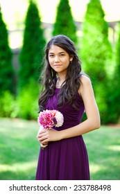 Beautiful biracial bridesmaid in purple dress, smiling outdoors