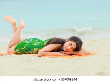 Beautiful biracial teen girl lying down on stomach sleeping  at tropical hawaiian beach with aqua blue ocean in background
