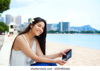 Beautiful biracial teen girl or young woman sitting on beach using tablet computer. Diamond Head and Waikiki in background
