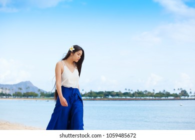Beautiful biracial teen girl or young woman wearing white top and blue flowing pants walking along Hawaiian beach with Waikiki and Diamond Head crater in background