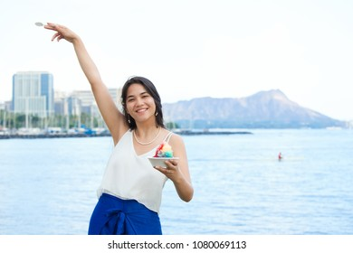 Beautiful biracial teen girl or young woman smiling and holding up bowl of shave ice in Hawaii. Diamond Head and Waikiki in background.