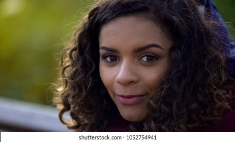 Beautiful biracial woman posing for camera and smiling sincerely, face close-up