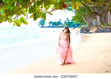 Beautiful biracial young woman with long hair walking on Hawaiian beach in pink dress or gown. Blue ocean waves in background.