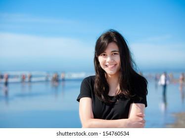 Beautiful biracial young woman or teen enjoying walk along beach by Pacific Ocean