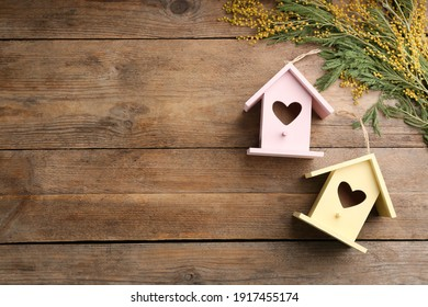 Beautiful bird houses with heart shaped holes and mimosa flowers on wooden background, space for text. Spring flat lay composition