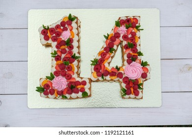 beautiful birthday cake in the form of the number fourteen on a Golden substrate top view
