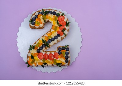 beautiful birthday cake in the form of numbers two on a lilac background