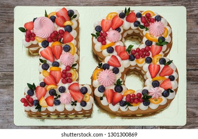 beautiful birthday cake in the shape of the number eighteen on a wooden background top view