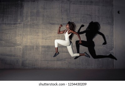 Beautiful Black African athletic girl does a dramatic leap with a light casting a shadow against a concrete wall in the background