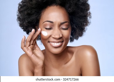 Beautiful black african model with flawless skin smooth complexion applying moisturiser face cream to her cheek, beauty cosmetics skincare concept