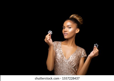 Beautiful Black Afro American Girl with hairstyle bunch and Luxurious make-up is posing with a bunch of Casino Chips in her hands. Casino, Poker and Roulette. Gambling dark-skinned Woman Lucky