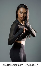 A beautiful black asian athletic woman with long black hair wearing all black sports wear shows a fighters stance with wrapping on her hands with an intimidating  stare at the camera