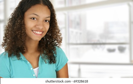Beautiful black college student on campus in front of window.