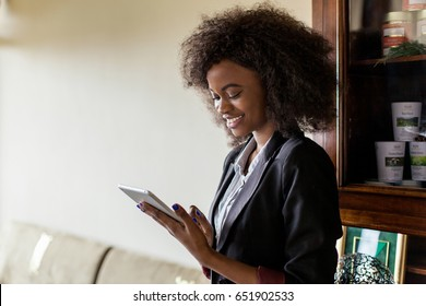 Beautiful black girl with curly hair standing in the room and holding a tablet. Girl wearing suit.