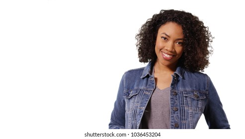Beautiful black girl in denim jacket smiling at camera on white background