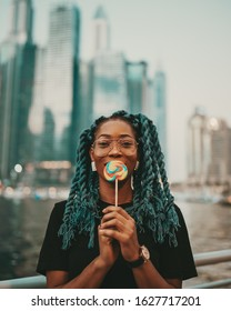 Beautiful black girl is licking lollipop or candy on dubai marina walk street with skyscrapers on the background