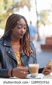 Beautiful black girl sitting outdoor with coffee looking at her mobile.