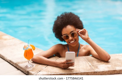 Beautiful black girl with tropical cocktail browsing internet on smartphone at outdoor swimming pool